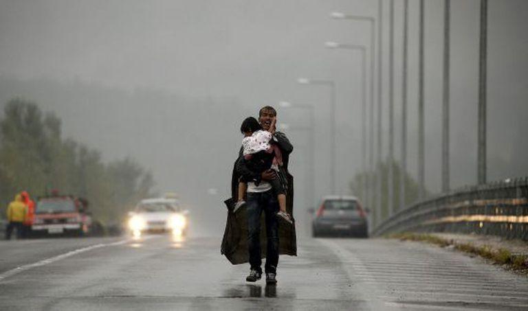 Um refugiado grita a seus companheiros para que esperem, enquanto caminha com sua filha no colo por uma estrada grega para a Macedônia.