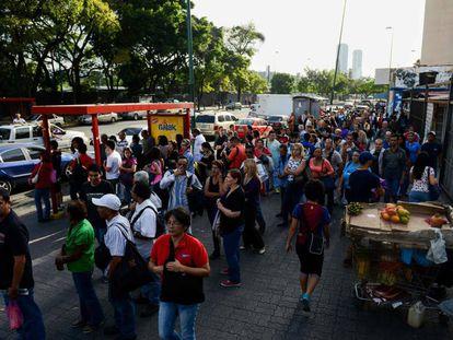 Um grupo de pessoas espera o ônibus em Caracas.