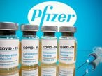 """FILE PHOTO: Vials with a sticker reading, """"COVID-19 / Coronavirus vaccine / Injection only"""" and a medical syringe are seen in front of a displayed Pfizer logo in this illustration taken October 31, 2020. REUTERS/Dado Ruvic/File Photo"""