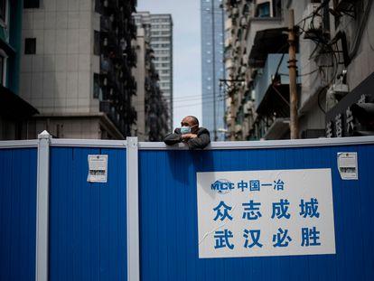 Um homem com máscara se debruça em uma barricada que impedia o acesso a um condomínio de Wuhan, em 14 de abril de 2020.