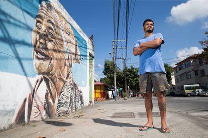 Wallace Pato, diante de uma pintura que fez em Ramos, no Rio.