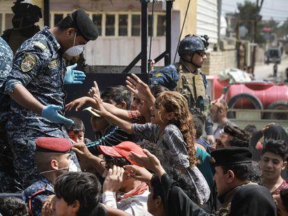 Polícia do Iraque distribui alimentos para a população no último dia 13.