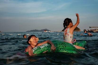 Duas meninas utilizam uma boia para flutuar na praia de Xichong.