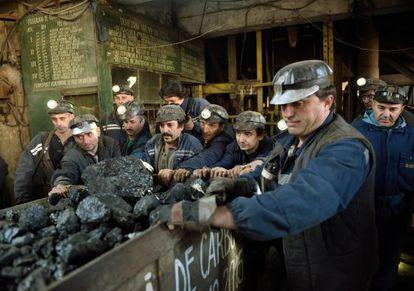 Mineiros rumanos empurram uma carruagem de carvão na localidade de Petrila