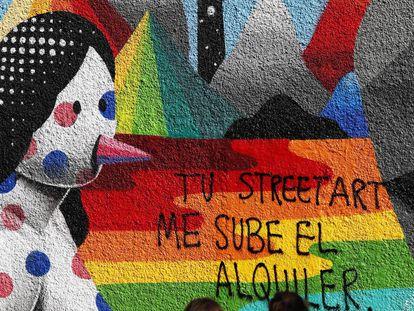 """""""Sua 'street art' sobe o meu aluguel"""", diz a pichação sobre um grafite de Okuda na rua Embajadores, em Madri."""