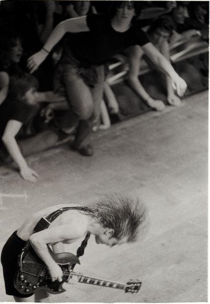 Fãs invadem o palco de um show do AC/DC, enquanto Angus Young fazia um solo de guitarra da turnê de 'Back In Black', em Londres, 1980.