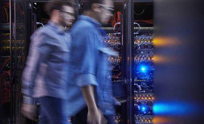 Dois técnicos caminham para a central de servidores