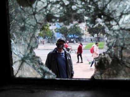 Um homem olha através da janela quebrada de uma delegacia de polícia destroçada logo depois de um protesto em Bogotá, em 5 de maio.