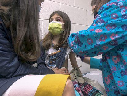 Alejandra Gerardo, de nove anos, olha para sua mãe enquanto é vacinada contra a covid-19 no hospital da Universidade de Duke, nos Estados Unidos. Alejandra e sua irmã gêmea, Marisol, são as primeiras crianças a receber a vacina da Pfizer nos EUA.