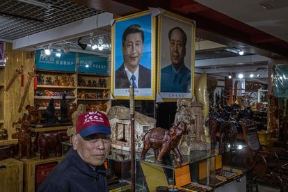 Um aposentado chinês passa em frente a imagens de Xi Jinping e Mao Tsé-tung, em uma loja de lembranças em Jinggangshan (China).