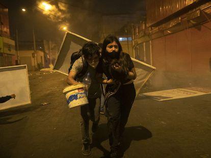 Dois jovens manifestantes procuram abrigo depois que a polícia os dispersou com gás lacrimogêneo em 14 de novembro.