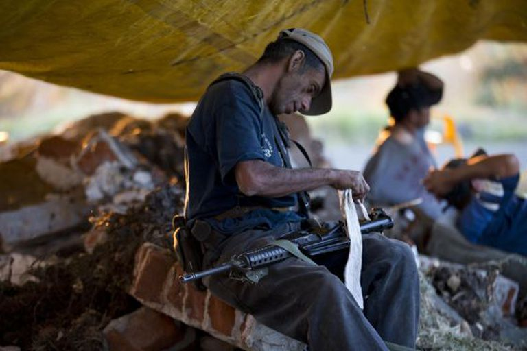 Um membro das milícias civis de Michoacán com a sua arma.